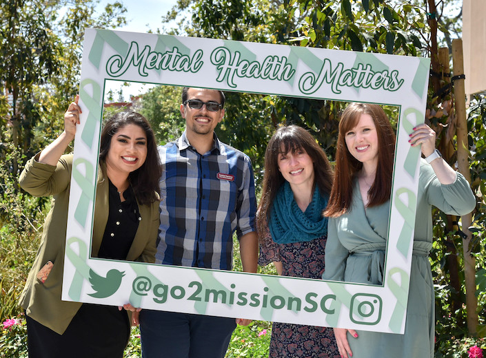 "Four people lean into a prop photo frame that reads ""Mental health matter!"" for a photo outside on campus."