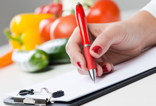 writing on paper with fruit in background