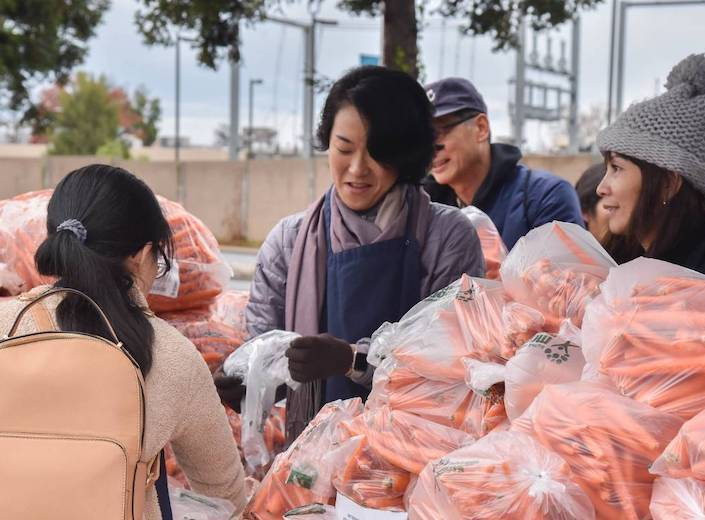 Women distribute bags of carrots at a Second Harvest food bank.